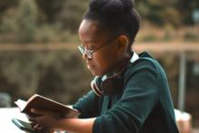 black girl with mobile and reader